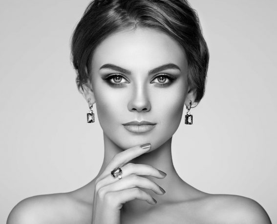 Portrait Beautiful Woman with Jewelry. Model Girl with Manicure on Nails. Elegant Hairstyle. Make-up Arrows. Beauty and Accessories. Black and White