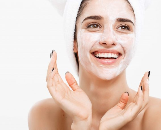 Beauty Skin Care Concept - Beautiful Caucasian Woman Face Portrait applying cream mask on her facial skin white background
