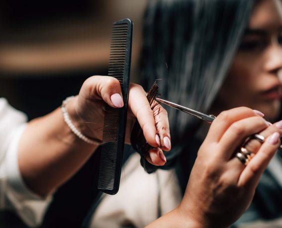 Woman getting a new haircut. Female hairstylist cutting her long black hair with scissors in hair salon