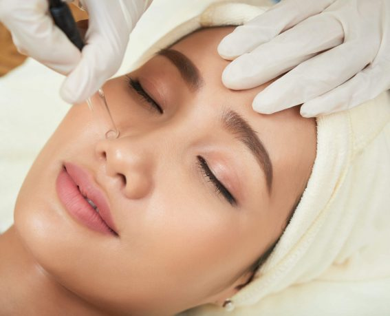 Face of attractive Vietnamese woman getting vacuum cleansing procedure